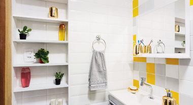 Banheiro pequeno com decoração em tons dourado e cinza