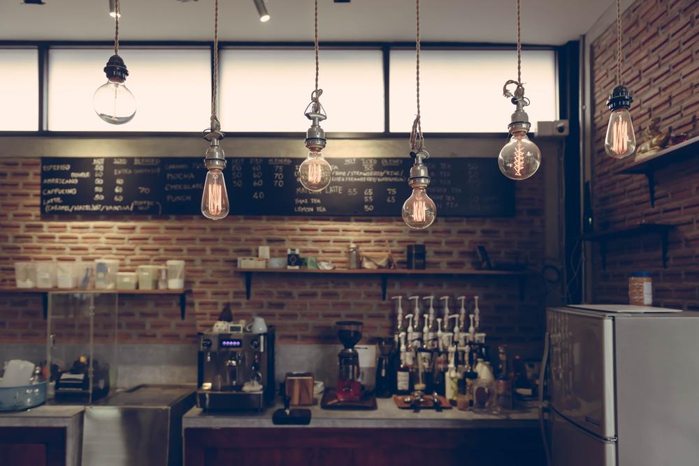 Decoração de cafeteria com luminárias de teto industriais