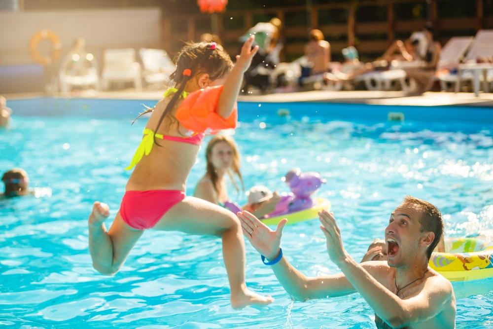 Crianças brincam na piscina usando bóias de braço.