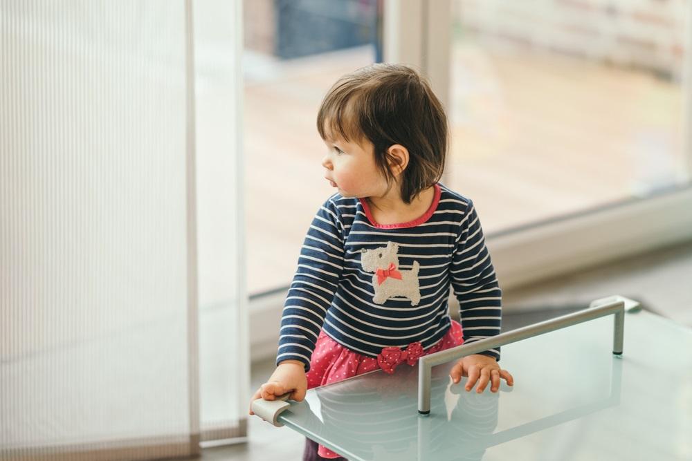 Criança próxima a uma mesa com proteção nas quinas.