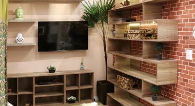 Sala de estar com estante e papel de parede de tijolo à vista